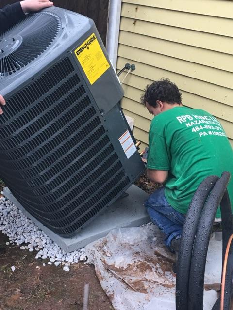 man installing AC unit for house