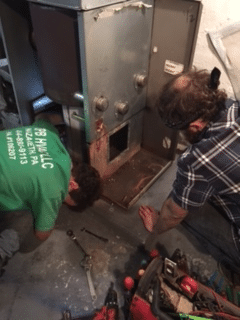 two men removing old water heater